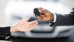Pessoa recebe as chaves de seu carro por assinatura.