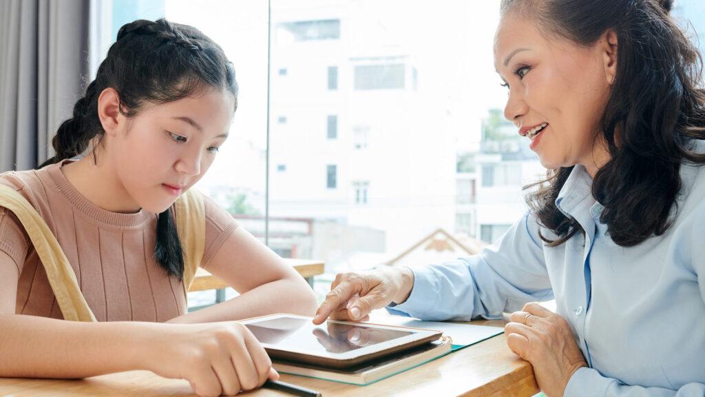 Professora conversa com aluna sobre mensalidades em atraso.