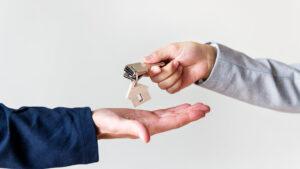 Corretor de imóveis assina contrato de aluguel com cliente.