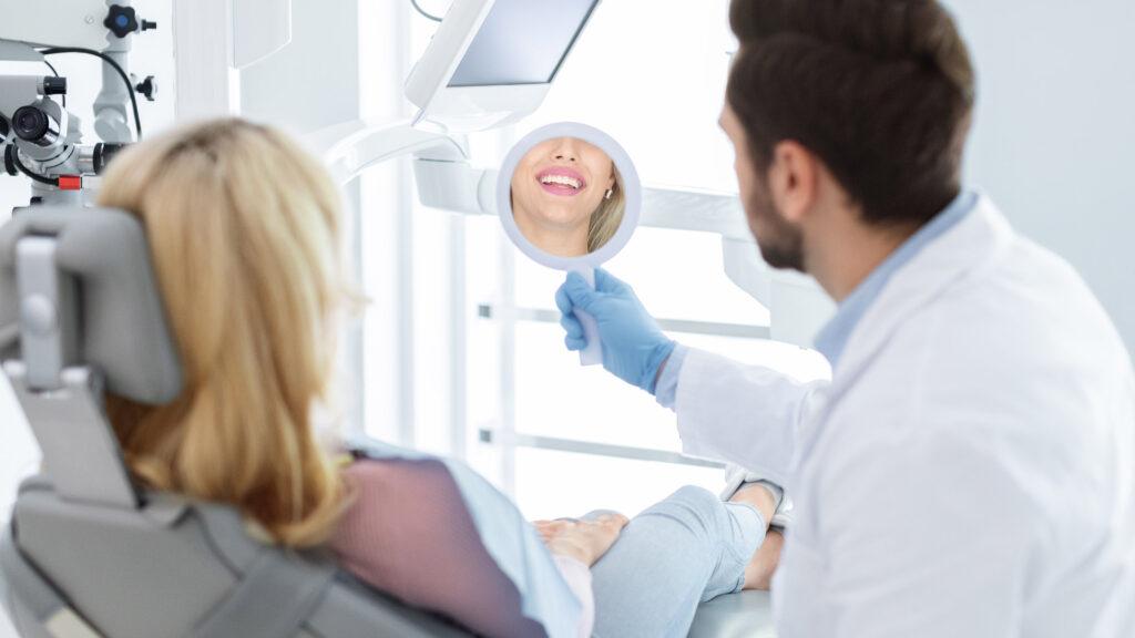 Dentista, dono de consultórios odontológicos, mostra à paciente o resultado do tratamento pago no modelo de cobrança recorrente.