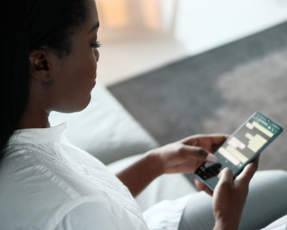 African American Woman Sitting On Couch, Using Mobile Phone For Text Messaging On Social Media. Over The Shoulders.